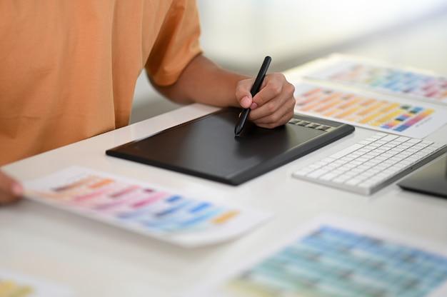Ręka z piórem piszącym na tablicy cyfrowej z kartą kolorów na biurku projektanta