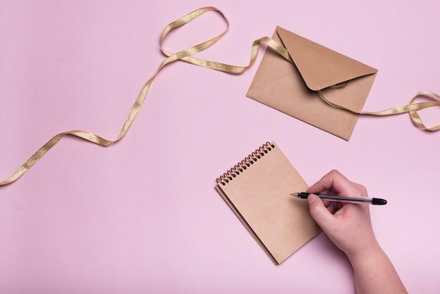 Ręka z piórem w pobliżu notebooka, koperty i wstążki