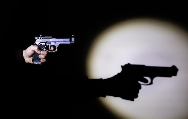 Ręka z pistoletem. cień w świetle reflektorów. pojęcie karne.