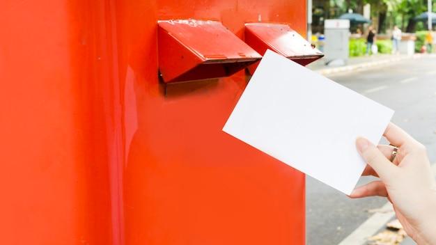 Ręka z pocztówki i upuść w czerwonym postbox
