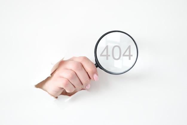 Ręka z podartego papieru wyciągając szkło powiększające
