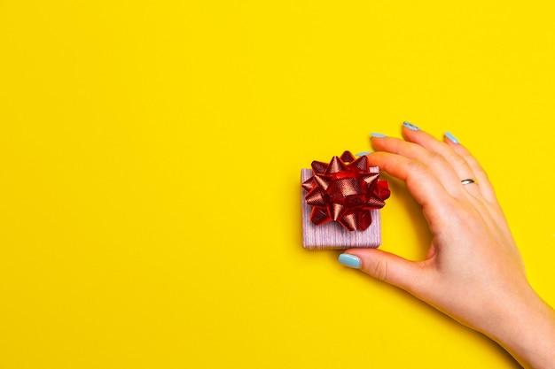 Ręka z pudełkiem prezentowym na żółtym tle z wolnym miejscem na tekst unboxing theme
