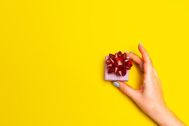 Ręka z pudełkiem prezentowym na żółtym tle z wolnym miejscem na tekstową listę prezentów, które chcesz