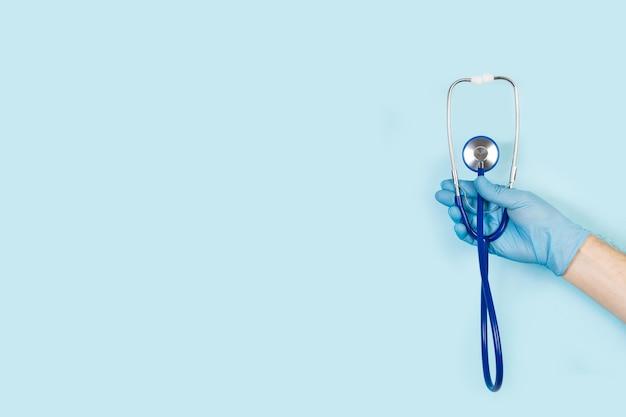 Ręka z rękawicą chirurgiczną trzymająca stetoskop na jasnoniebieskiej powierzchni