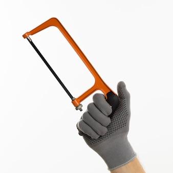 Ręka z rękawicą trzyma piłę