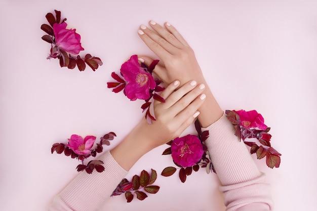 Ręka z różowe kwiaty i płatki leżące na tle papieru. kosmetyki do pielęgnacji skóry dłoni. naturalne kosmetyki z płatków, olejki eteryczne, przeciwzmarszczkowa i przeciwstarzeniowa pielęgnacja dłoni