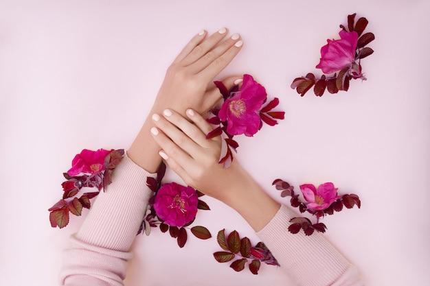 Ręka z różowymi kwiatami i płatkami kłama na papierowej powierzchni. kosmetyki do pielęgnacji skóry dłoni. naturalne kosmetyki płatkowe, olejki eteryczne, pielęgnacja dłoni przeciwzmarszczkowa i przeciwstarzeniowa