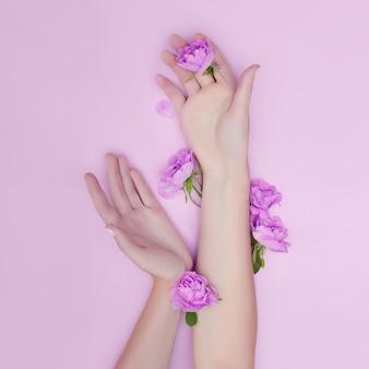 Ręka z różowymi kwiatami i płatkami kłama na papierowej ścianie. kosmetyki do pielęgnacji skóry dłoni. naturalne kosmetyki płatkowe, olejki eteryczne, pielęgnacja dłoni przeciwzmarszczkowa i przeciwstarzeniowa