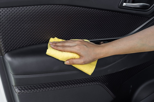 Ręka z ściereczką z mikrofibry do czyszczenia wnętrza drzwi samochodu