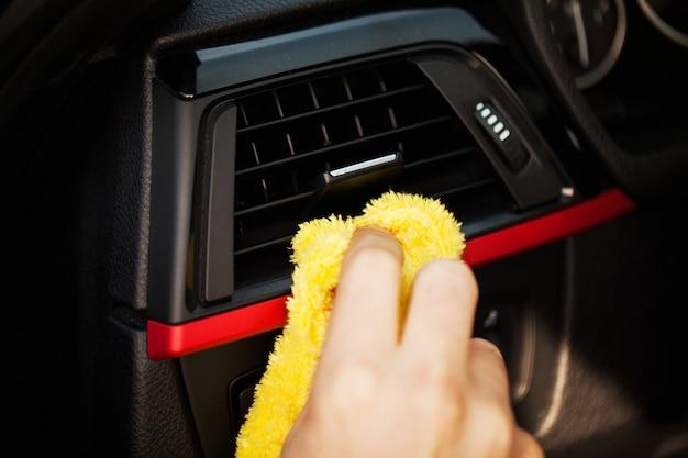 Ręka z ściereczką z mikrofibry do czyszczenia wnętrza samochodu