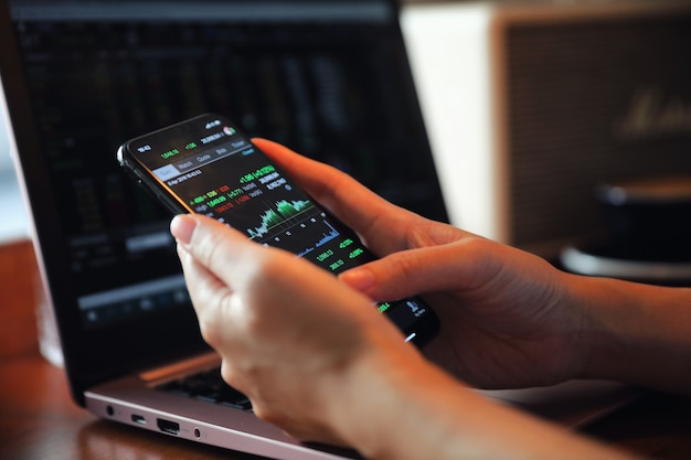Ręka z smartphone handlu akcji online w kawiarni, koncepcja biznesowa