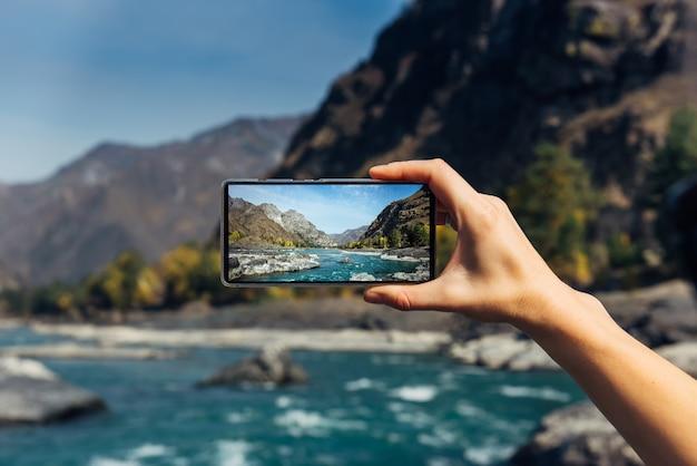 Ręka z smartphone z bliska. robienie zdjęć na smartfonie podczas podróży. wspaniały krajobraz górski, burzliwa rzeka, skały i błękitne niebo