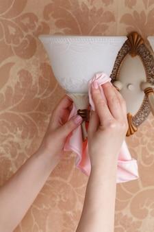 Ręka z suchą ściereczką z mikrofibry czyszczącą żyrandol w pokoju.