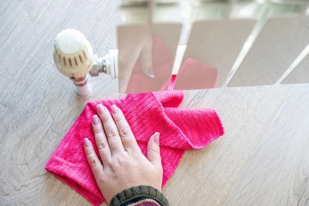 Ręka z szmatką do czyszczenia wody z nieszczelności grzejnika