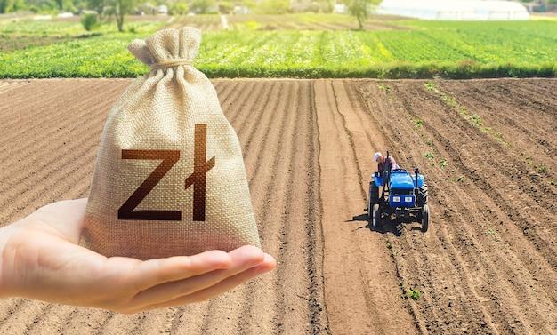 Ręka z woreczkiem na złotówki na tle pola rolniczego z traktorem dzierżawa ziemi