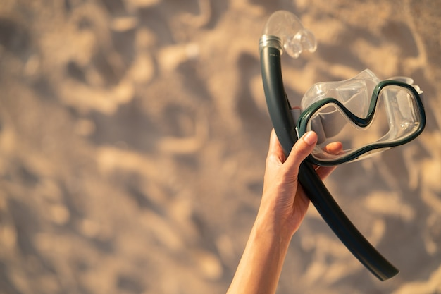 Ręka z wyposażeniem do maski do snorkelingu na plaży.