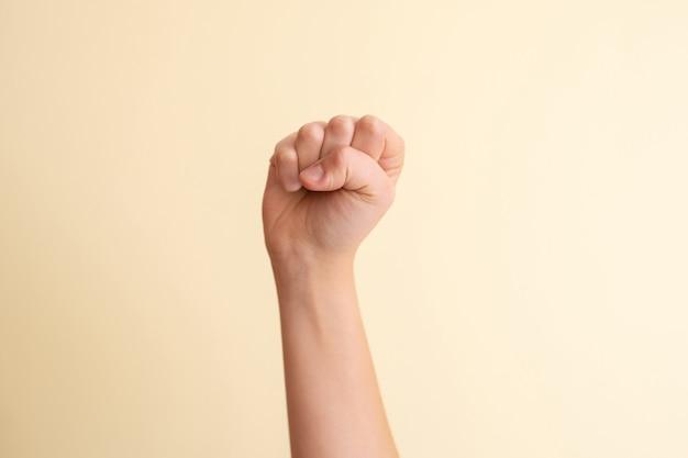 Ręka z zaciśniętą pięścią na żółtym tle