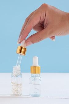 Ręka z zakraplaczem olejku eterycznego, esencji do aromaterapii, serum kosmetycznego lub płynu leczniczego na beżowym tle. butelki niemarkowe do twojego projektu.