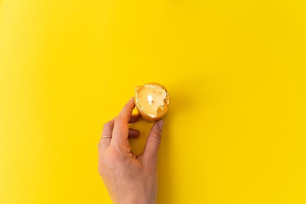 Ręka z złotymi świeczkami na kolor żółty powierzchni. wellnes, magia, relaks koncepcja.