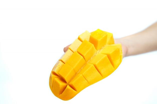 Ręka z żółtym mango i mango plasterkiem na sześcianach odizolowywających