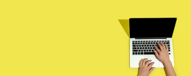 Ręka za pomocą gadżetów, laptopa na widoku z góry, pustego ekranu z copyspace, minimalistyczny styl. technologie, nowoczesne, marketingowe. negatywne miejsce na reklamę, ulotkę. żółty kolor na tle. stylowy, modny.