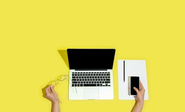 Ręka za pomocą gadżetów, urządzeń na widoku z góry, pustego ekranu z copyspace, minimalistyczny styl. technologie, nowoczesne, marketingowe. negatywne miejsce na reklamę, ulotkę. żółty kolor na tle. stylowy, modny.