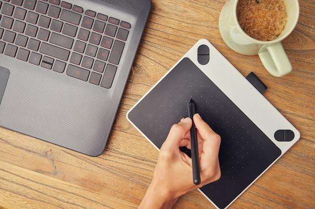 Ręka za pomocą rysowania tabletu na biurku, obok laptopa i filiżankę kawy. drewniane biurko.