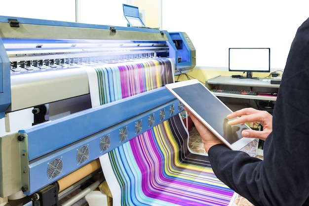 Ręka za pomocą sterowania tabletu z drukarką atramentową drukującą wielokolorowy winyl
