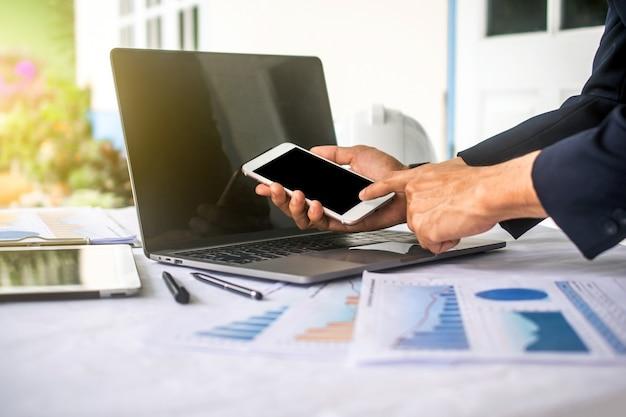 Ręka za pomocą telefonu komórkowego w biurze z laptopem