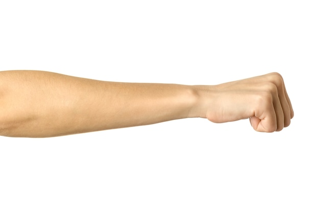 Ręka zaciśnięta w pięść. obraz poziomy. kobieta ręka z francuskim manicure gestykuluje na białym tle na białej ścianie. część serii