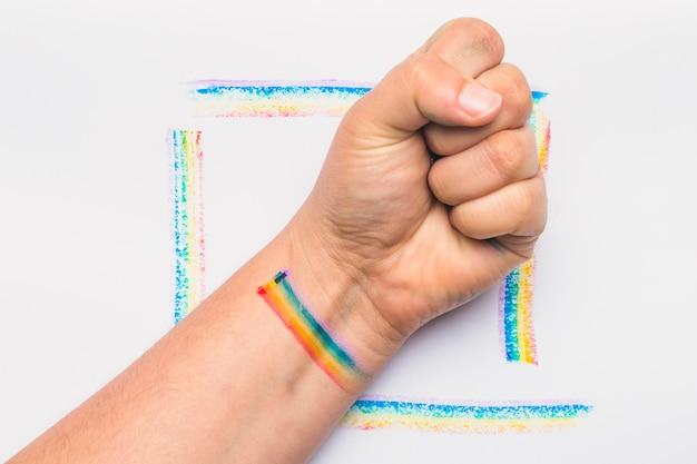 Ręka zaciśnięta w pięść w paski w kolorach lgbt