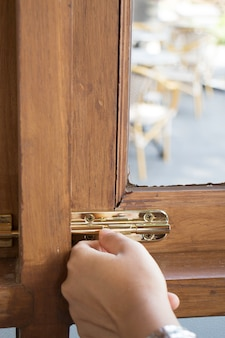 Ręka zamknięta na drewnianej ramie okna