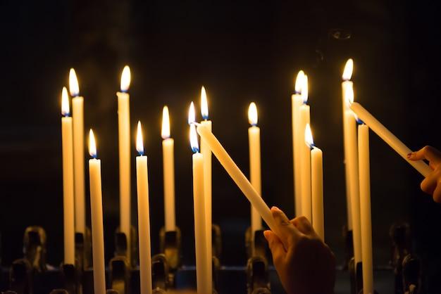 Ręka zapala świeczki w kościele na czarnym tle