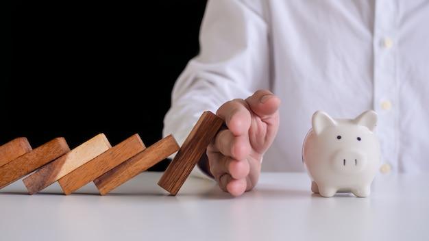 Ręka zapobiegająca wpadaniu domina do skarbonki. zapobieganie zagrożeniom zewnętrznym. plan ubezpieczenia pieniędzy