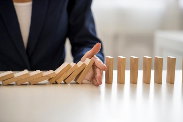 Ręka zatrzymując spadające bloki na stole