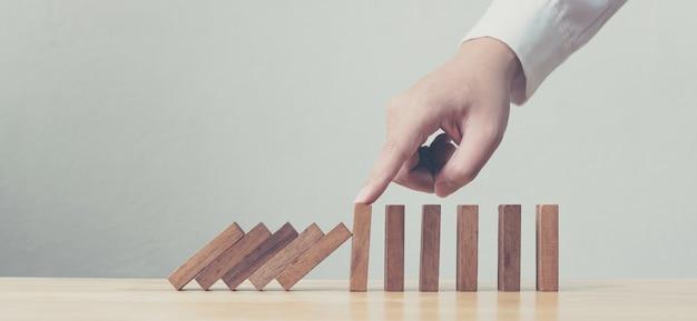 Ręka zatrzymująca efekt kryzysu biznesowego drewnianego domina