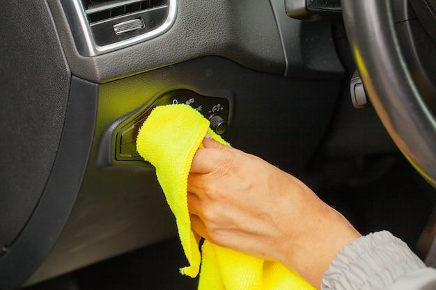 Ręka ze ściereczką z mikrofibry do czyszczenia wnętrza nowoczesnego samochodu.