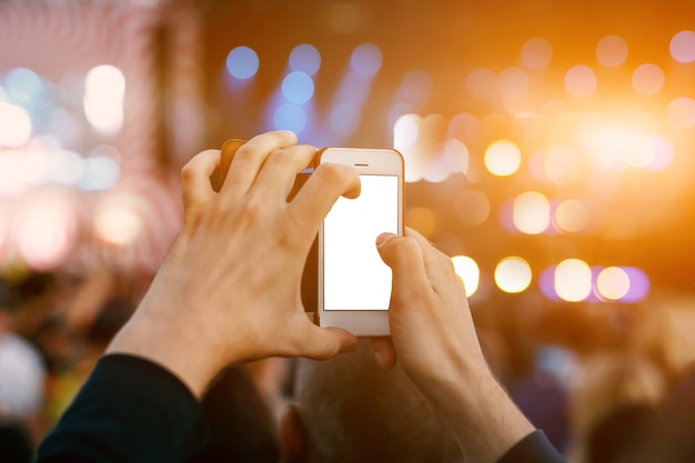 Ręka ze smartfonem nagrywa festiwal muzyki na żywo