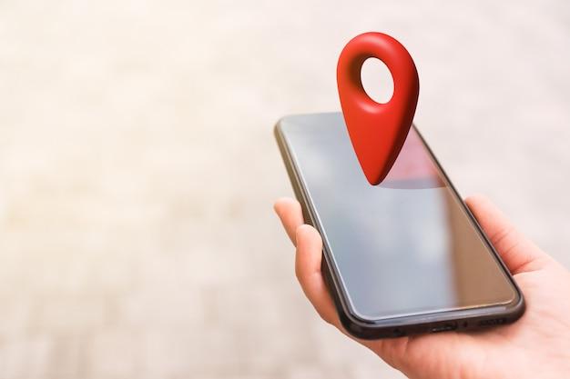 Ręka ze smartfonem z czerwoną pinezką lokalizatora 3d na górze