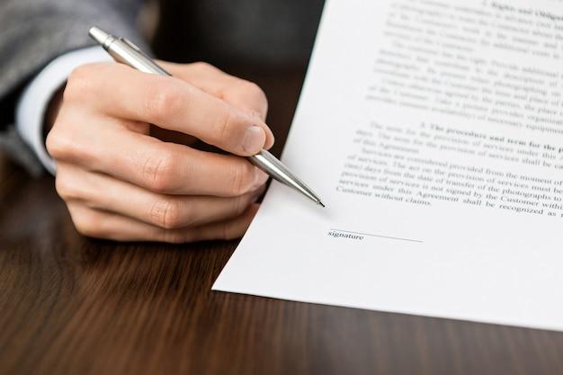Ręka ze srebrnym długopisem wskazuje puste miejsce na podpis