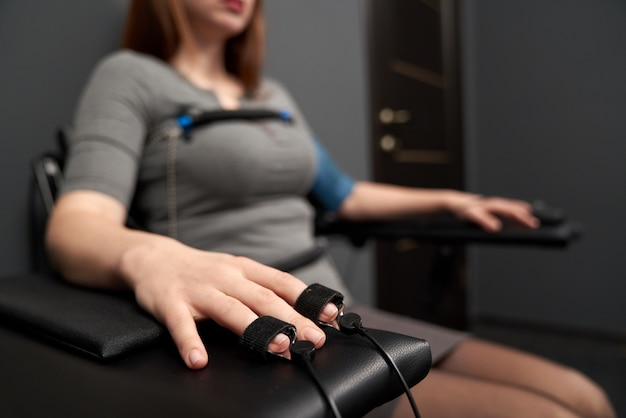 Ręka ze wskaźnikiem pomiaru pulsu podczas testu wykrywacza kłamstw