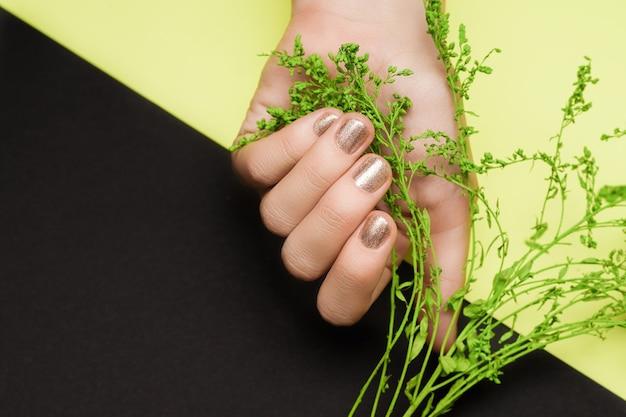 Ręka ze złotym wzorem paznokci. złota ręka. ręka na zielonej czarnej powierzchni.