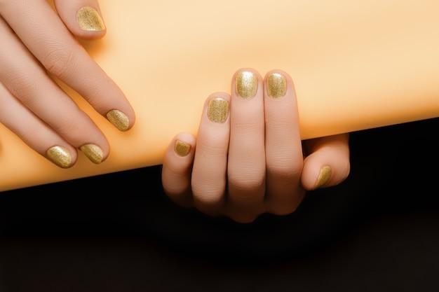 Ręka ze złotym wzorem paznokci. złote ręce kobiece trzymają pomarańczowy papier na czarnej powierzchni.