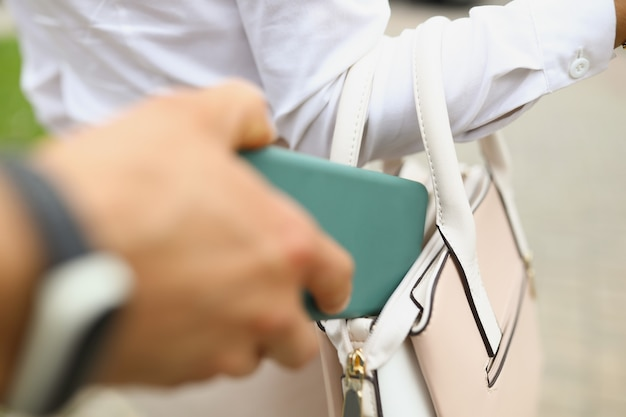 Ręka złodzieja kradnie portfel z kobiecej torby widok z tyłu przestępca kradnie smartfona
