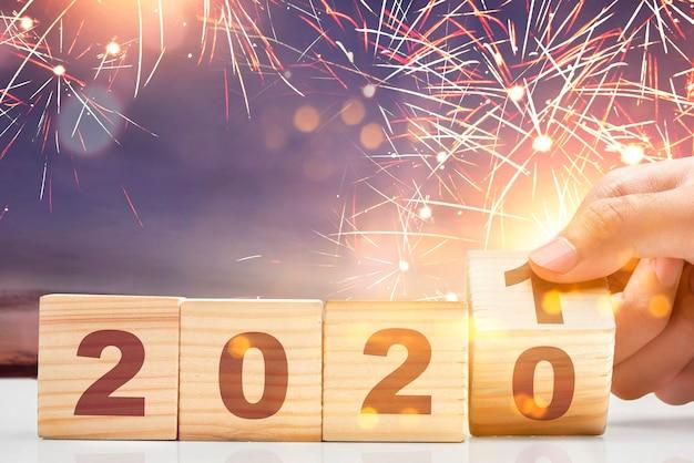 Ręka zmienia drewnianą kostkę z 2020 na 2021. szczęśliwego nowego roku 2021