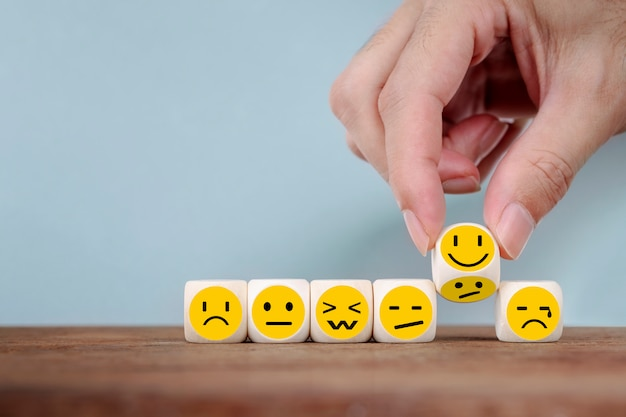 Ręka zmienia z uśmiechu emoticon ikonami