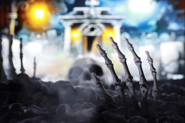Ręka zombie szkieletu wyłaniająca się z cmentarza - halloween