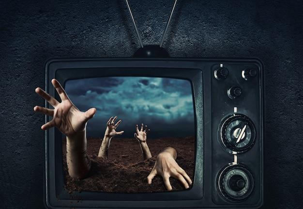 Ręka zombie wychodząca z grobu z telewizora, noc halloween