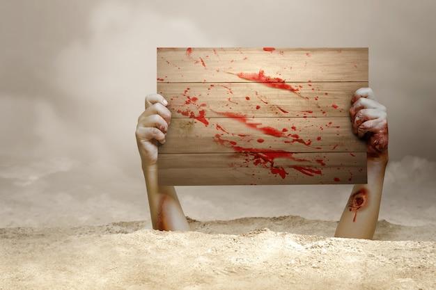 Ręka zombie z krwią i raną podniesiona z ziemi trzymająca drewniany szyld na mglistym tle