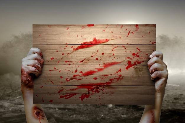 Ręka zombie z krwią i raną trzymająca drewniany szyld z dramatycznym tłem sceny